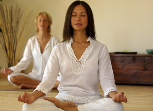 Two women using breathing techniques to de-stress